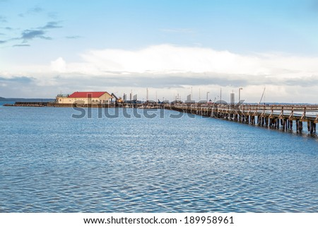Bridge or pier stretching diagonally across an expanse of calm tranquil blue sea with a rippling surface under a cloudy blue sunny sky in a beautiful background image - stock photo