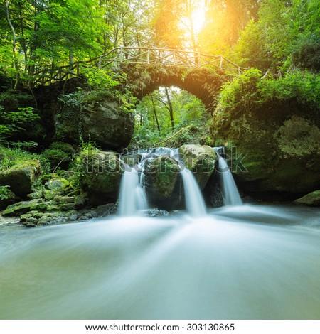 Bridge over a fairy tale waterfall - stock photo