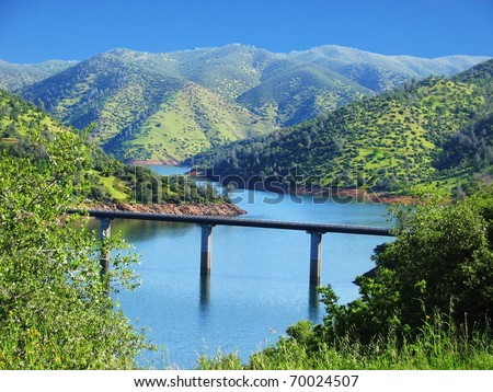 Bridge Over a River Surrounded by green hills at Yosemite National Park