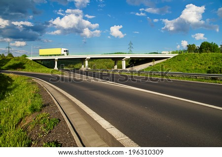 Bridge over an empty highway in the countryside, going over the bridge truck, blue sky with white clouds - stock photo