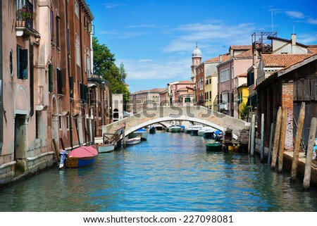 Bridge over canal with boats in Venice