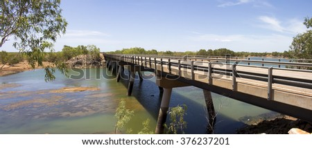 Bridge over Cockatoo Creek on the Great Northern Highway near Willare Crossing between Broome and Derby  North Western Australia on a cloudy very hot morning in the tropical summer Wet Season. - stock photo