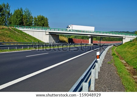 Bridge over empty highway in the countryside, the bridge rides white truck - stock photo