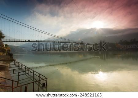 Bridge over Ganga River in Rishikesh, India - stock photo