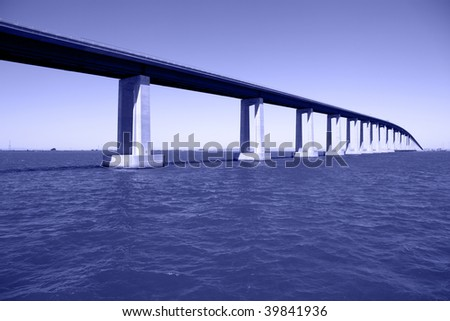 Bridge over San Joaquin River Delta at Antioch California, high enough at apex to allow seagoing cargo vessels to pass beneath. - stock photo