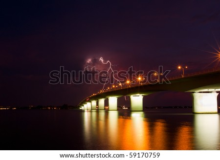 Bridge over the bay struck with twin lightning bolts after sunset - stock photo