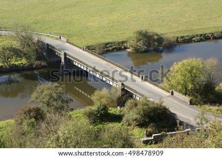 Bridge over the river Towy. Reflective still water with green fields and trees.