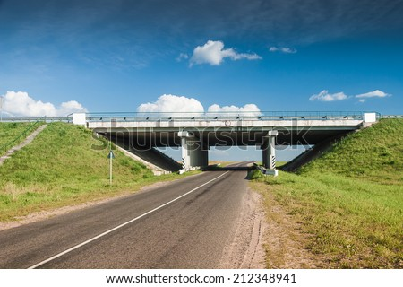 Bridge over the rural road at sunny day - stock photo