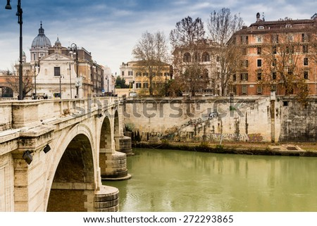 Bridge over the Tiber river in the center of Rome. Basilica of St. Peter in the background