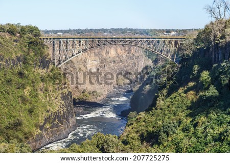 Bridge over the Zambezi River near Victoria Falls. The Victoria falls is the largest curtain of water in the world  (1708 meters wide) - Zambia, Zimbabwe - stock photo