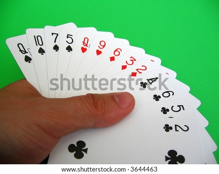 bridge playing - one hand (Q,10,7,5 spades, Q,9 hearts, 6,3,2 diamonds, A,6,5 clubs)  background green, selective focus, - stock photo