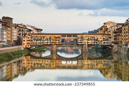 Bridge Ponte Vecchio with reflection in Arno river in Florence, Italy.