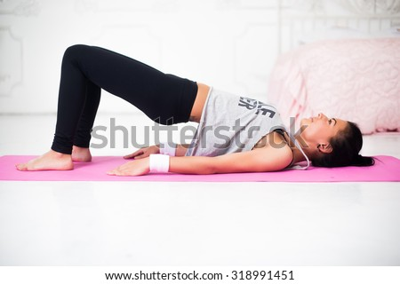 Bridge pose sporty woman doing warming up exercise for spine, backbend, arching stretching her back  working out at home fitness workout yoga gymnastics concept. - stock photo