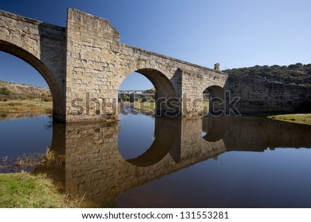 Bridge reflected in water Old bridge over  river in Spain, and two new ones at bottom - stock photo