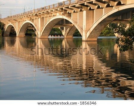 Bridge reflecting on the colorado river peacefully, uniting south Austin and north Austin. - stock photo