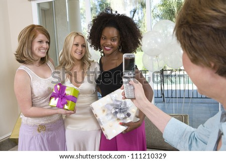 Bridge's mother photographing bride and her friends through mobile phone at party - stock photo