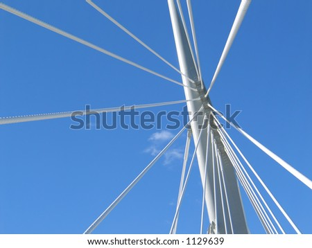 Bridge spire with cables, from below, against a blue summer sky.