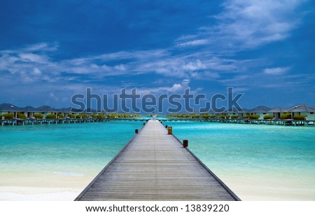 Bridge to water bungalows in the indian ocean - stock photo