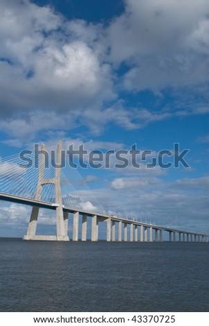 Bridge Vasco da Gama  Lisbon Portugal Blue Sky White Clouds - stock photo