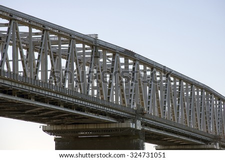 Bridge with bridge-walking bridge and small people in gray coveralls on top of the Old Little Belt Bridge.