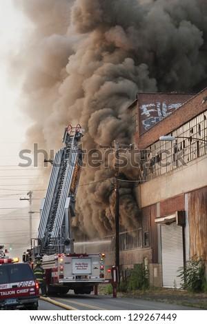 BRIDGEPORT, CT , U.S. - JUNE 21:  The Bridgeport Fire Department battles a large factory fire on Hancock Avenue in Bridgeport, Ct. on June 21, 2012. - stock photo