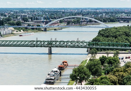 Bridges over the Danube river in Bratislava city, Slovak republic. Old bridge and Apollo bridge. Ship transportation. Capital city of Slovakia. Travel destination. - stock photo