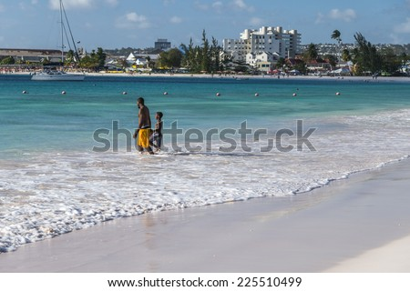 BRIDGETOWN, BARBADOS - FEBRUARY 23, 2014 : Man and his son enjoying a swim in the ocean at Browne's Beach in Carlisle Bay, Bridgetown in Barbados West Indies. - stock photo