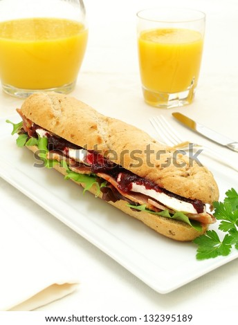 brie and bacon baguette on platter with orange juice - stock photo