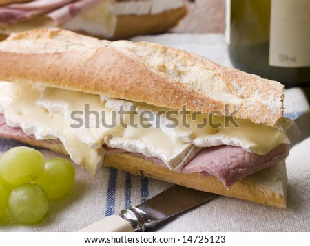 Brie and Ham Baguette with White Wine and Grapes - stock photo