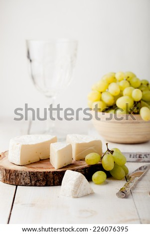 Brie, camembert cheese with fresh grape  on a wooden board with wine glass on a white background - stock photo
