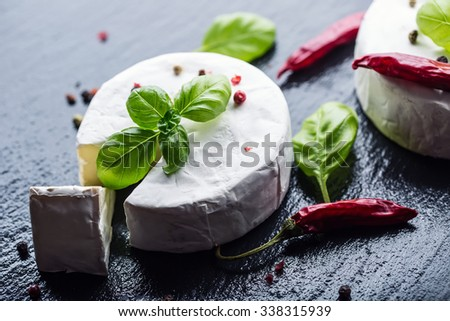Brie cheese. Camembert cheese. Fresh Brie cheese and a slice on a granite board with basil leaves four colors pepper and chili peppers. Italian and Mediterranean ingredients. - stock photo