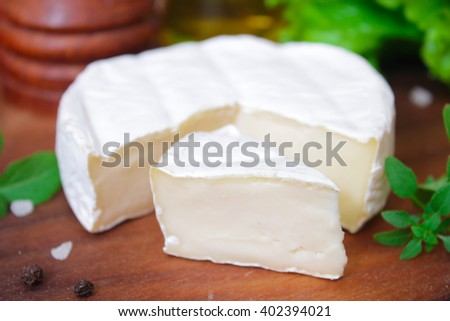 Brie cheese. Camembert cheese. Fresh Brie or Camembert cheese with basil leaves. Italian, French and Mediterranean ingredients.  - stock photo