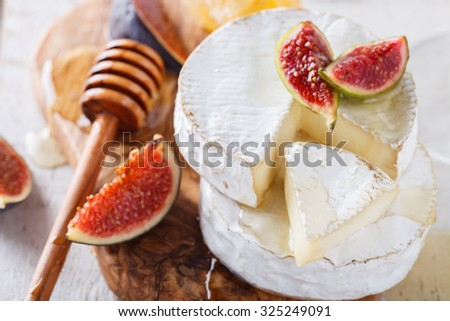 Brie cheese on a wooden Board with fresh figs and honey.selective focus. - stock photo