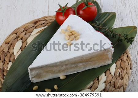 Brie cheese on bamboo leaves with cedar nuts