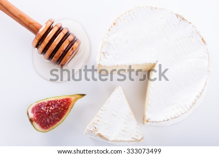 Brie cheese on with a white background with fresh figs and honey.selective focus. - stock photo