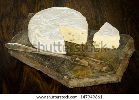 Brie cheese with a wedge cut out on a slate  - stock photo