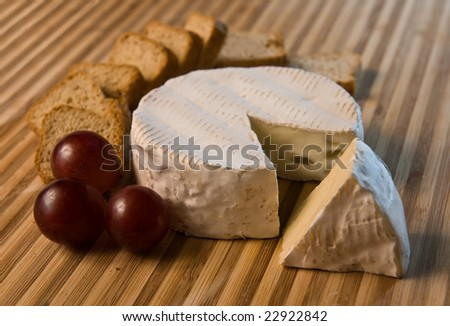 brie cheese with crusts and grape on bamboo board - stock photo