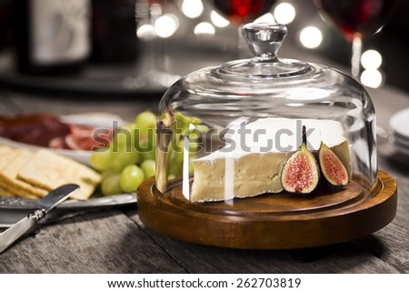 Brie Cheese with Figs, Wine, and Tray of Party Snacks with Festive Lights in the Background - stock photo