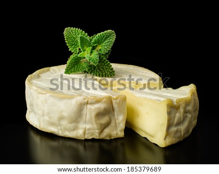 brie cheese with fresh mint on black background - stock photo