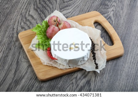 Brie cheese with grape and cedar nuts - stock photo