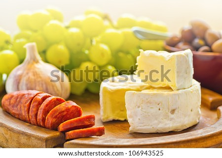 Brie cheese with olives and chorizo on a wooden plate - stock photo