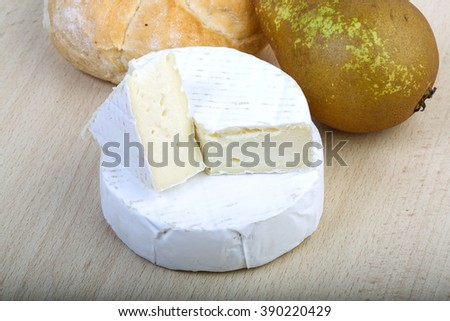 Brie cheese with pear and bread on the wood background