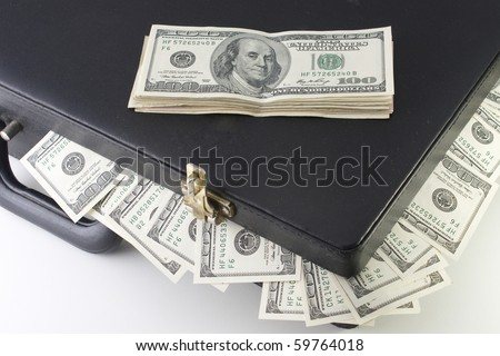 briefcase full of dollars with a stack of bills over - stock photo