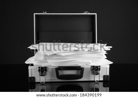 Briefcase full of papers, isolated on black