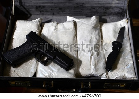 briefcase with drugs, gun, and a knife. - stock photo