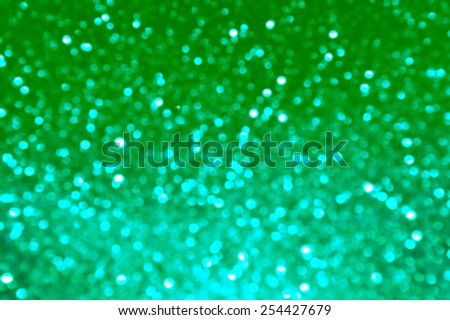 Bright and abstract blurred green and blue background with shimmering glitter - stock photo