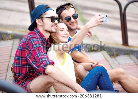 Bright and cheerful day. Young friends have fun together on the street and smile at each other. Funny guys make Selfie