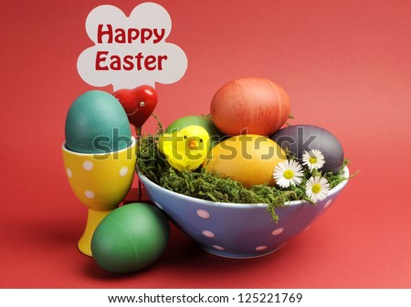 Bright and cheerful Easter still life with rainbow color eggs in blue polka dot bowl, with Happy Easter sign, against a red background. - stock photo