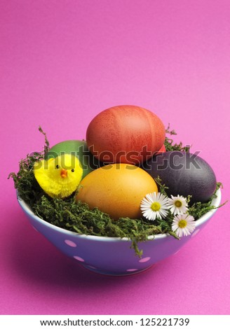 Bright and cheerful Happy Easter still life with rainbow color eggs in blue polka dot bowl against a pink background. Portrait orientation. - stock photo