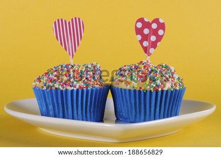 Bright and cheery red blue and yellow theme cupcakes with hundred and thousands candy topping and heart toppers for birthday or special occasion on yellow background. - stock photo